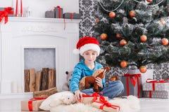 Милый счастливый мальчик в шляпе santa с подарками на рождество игрушки Стоковое Изображение RF