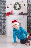 Милый счастливый мальчик в шляпе santa с подарками на рождество игрушки Стоковые Изображения RF