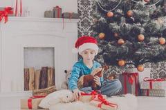 Милый счастливый мальчик в шляпе santa с подарками на рождество игрушки Стоковые Фотографии RF