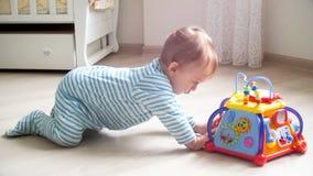 Милый 1-ти летний ребёнок вползая на поле к красочной игрушке Стоковое Изображение RF