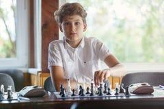Милый, умный, 11 лет старого мальчика в белой рубашке сидят в классе и играют шахматы на доске Тренировка, урок, хобби стоковая фотография rf