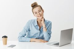 Милый усмехаясь женский независимый удаленный работник носит стекла используя кофе ноутбука выпивая проверяя электронные почты че стоковая фотография rf