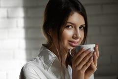 Милый усмехаясь кофе девушки выпивая в утре Стоковые Фотографии RF