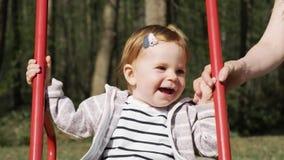 Милый усмехаясь маленький ребёнок отбрасывая на качании в летнем дне движение медленное акции видеоматериалы