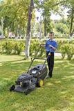 Милый усмехаясь мальчик работая с газонокосилкой стоковое изображение