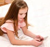 Милый усмехаясь ребенок маленькой девочки с ее смартфоном мобильного телефона стоковое изображение rf