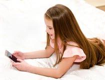Милый усмехаясь ребенок маленькой девочки с ее смартфоном мобильного телефона стоковые изображения rf