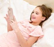 Милый усмехаясь ребенок маленькой девочки с ее смартфоном мобильного телефона стоковые фото