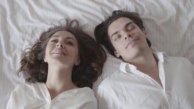 Милый человек и женщина падая на кровать и смотря один другого с любовью Молодые пары лежа в кровати Предложение видеоматериал