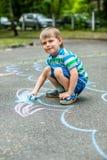 Милый чертеж мальчика и девушки с мелом на тротуаре в парке Стоковое фото RF