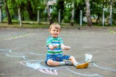 Милый чертеж мальчика и девушки с мелом на тротуаре в парке Стоковое Изображение RF