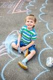 Милый чертеж мальчика и девушки с мелом на тротуаре в парке Стоковая Фотография RF