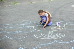 Милый чертеж мальчика и девушки с мелом на тротуаре в парке Стоковые Фото
