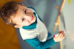 Милый чертеж мальчика на белой доске с ручкой и усмехаться войлока Стоковое Фото