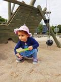 Милым малыш наблюданный коричневым цветом на спортивной площадке города Стоковые Фото