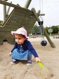 Милым малыш наблюданный коричневым цветом на спортивной площадке города Стоковое фото RF