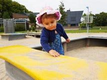 Милым малыш наблюданный коричневым цветом на спортивной площадке города Стоковое Фото