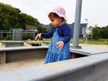 Милым малыш наблюданный коричневым цветом на спортивной площадке города Стоковые Изображения