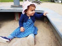 Милым малыш наблюданный коричневым цветом на спортивной площадке города Стоковые Изображения RF