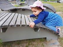Милым малыш наблюданный коричневым цветом на спортивной площадке города Стоковая Фотография RF