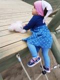 Милым малыш наблюданный коричневым цветом на спортивной площадке города Стоковое Изображение