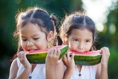 2 милых азиатских девушки маленьких ребенка есть свежие фрукты арбуза Стоковое фото RF