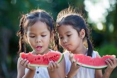 2 милых азиатских девушки маленьких ребенка есть свежие фрукты арбуза Стоковая Фотография