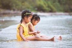 2 милых азиатских девушки маленьких ребенка сидя и играя с песком Стоковые Фотографии RF