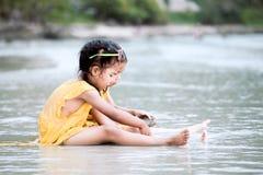 2 милых азиатских девушки маленьких ребенка сидя и играя с песком Стоковое Фото