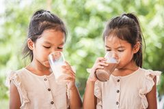 2 милых азиатских девушки ребенка выпивая молоко от стекла совместно стоковое изображение
