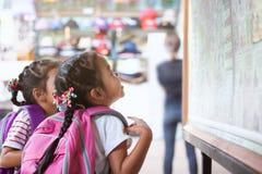 2 милых азиатских девушки ребенка при рюкзак смотря карту стоковые фотографии rf