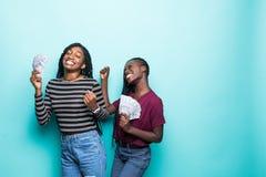 2 милых африканских друз маленьких девочек стоя показывающ банкноты денег, праздновать изолированный над зеленой предпосылкой стоковое изображение