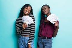 2 милых африканских друз маленьких девочек стоя показывающ банкноты денег, праздновать изолированный над зеленой предпосылкой стоковые фото
