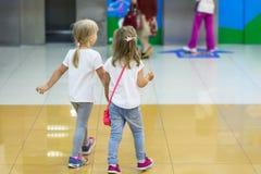 2 милых белокурых маленькой девочки идя совместно в мол Пары друзей ребенк держа руки во время прогулки Приятельство малыша стоковое фото rf