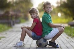 2 милых белокурых счастливых маленького ребенка, усмехаясь мальчик и длинн-с волосами сидеть девушки спиной к спине на футбольном стоковое изображение rf
