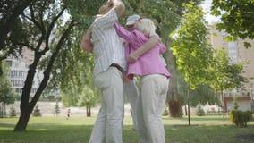 2 милых взрослых пары обнимая в парке совместно стоя в круге Двойная дата старших пар Дружелюбная компания акции видеоматериалы