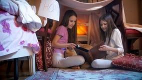 2 милых девушки в пижамах сидя в selfmade шатре в спальне и читая большую книгу Стоковые Фотографии RF