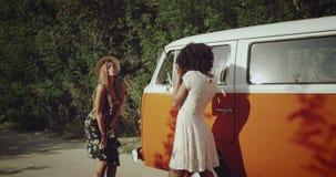 2 милых девушки делая фотосессию на дороге около винтажной оранжевой шины, счастливые танцы и усмехаясь, нося boho сток-видео