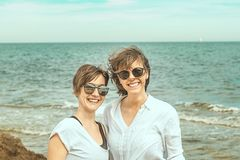 2 милых девушки на пляже усмехаясь и смотря один другого Стоковое Изображение RF