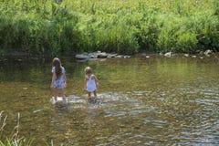 2 милых девушки на реке наслаждаются водами и природой Стоковые Фотографии RF