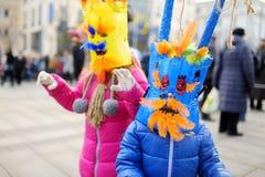 2 милых девушки нося пугающие маски во время торжества Uzgavenes, литовского ежегодного фольклорного фестиваля случаясь 7 Стоковая Фотография