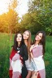 3 милых девушки стоя в шотландке outdoors, лучших другах имея потеху и смеясь над в парке Стоковые Фото