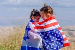 2 милых девушки с американскими и израильскими флагами 2 нации одна концепция сердца стоковое изображение rf