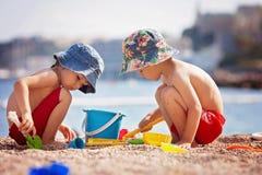 2 милых дет, играя в песке на пляже Стоковые Фото