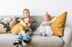 2 милых дет и большого бульдог на софе против белой стены Стоковые Изображения RF