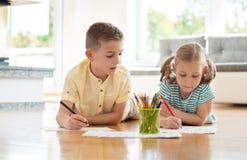 2 милых дет рисуют с красочными карандашами дома Стоковая Фотография RF