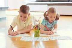 2 милых дет рисуют с красочными карандашами дома Стоковое Изображение RF