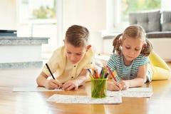 2 милых дет рисуют с красочными карандашами дома Стоковые Фото
