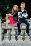 2 милых дет сидят на перилах фонтан Мрамор-камня Стоковые Изображения