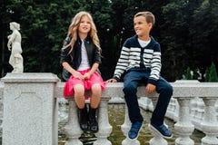 2 милых дет сидят на перилах фонтан Мрамор-камня Стоковое Фото